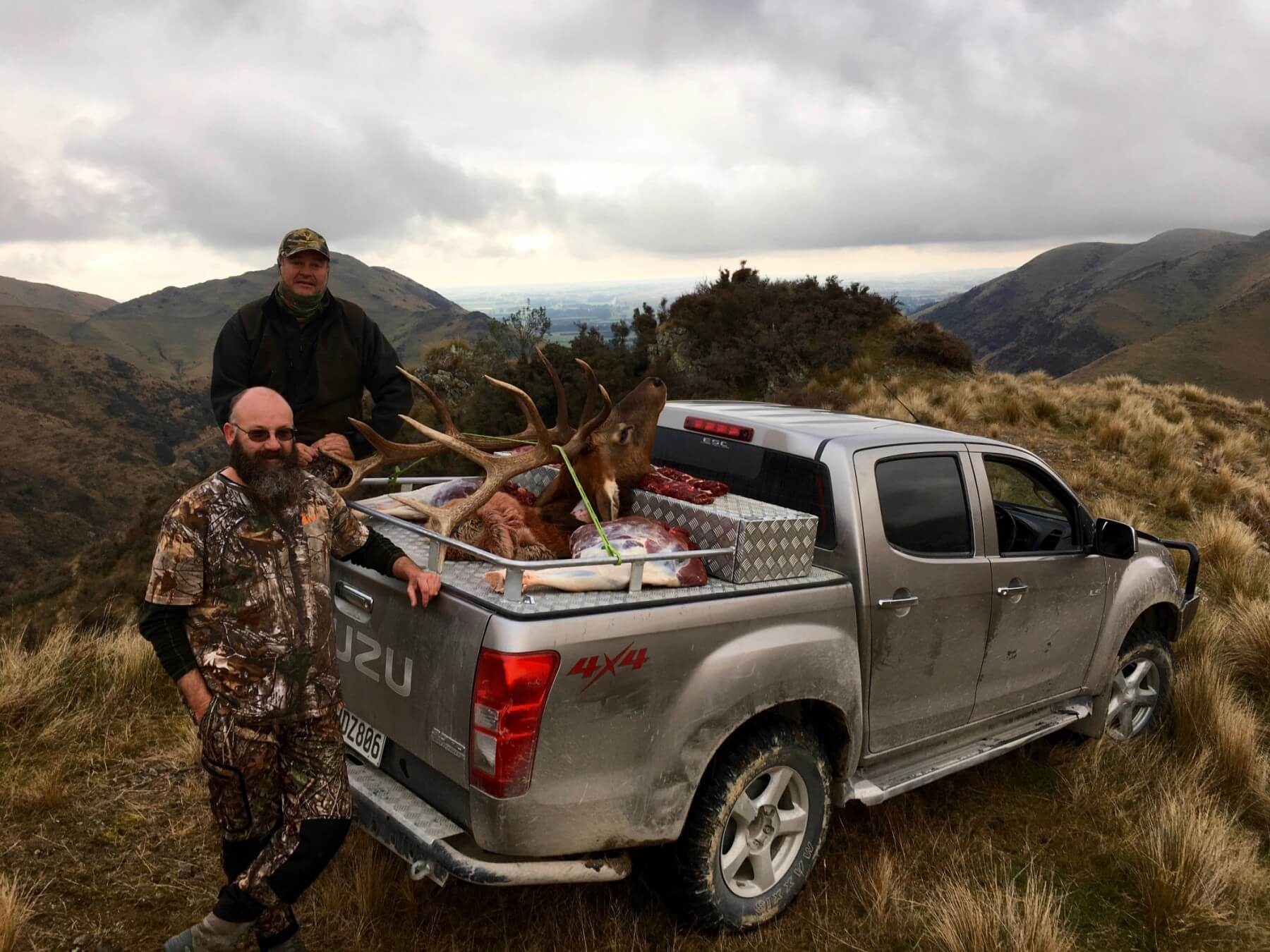 elk hunters with trophy on truck